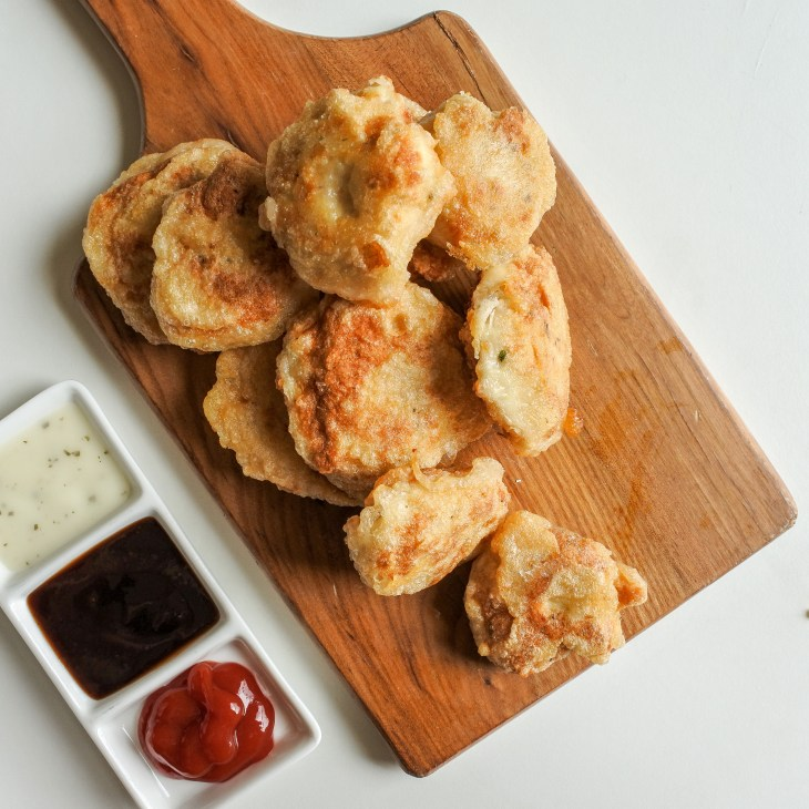chicken nuggets on board with dipping sauces