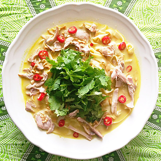 curried chicken soup with noodles, shredded chicken, red chiles and fresh cilantro