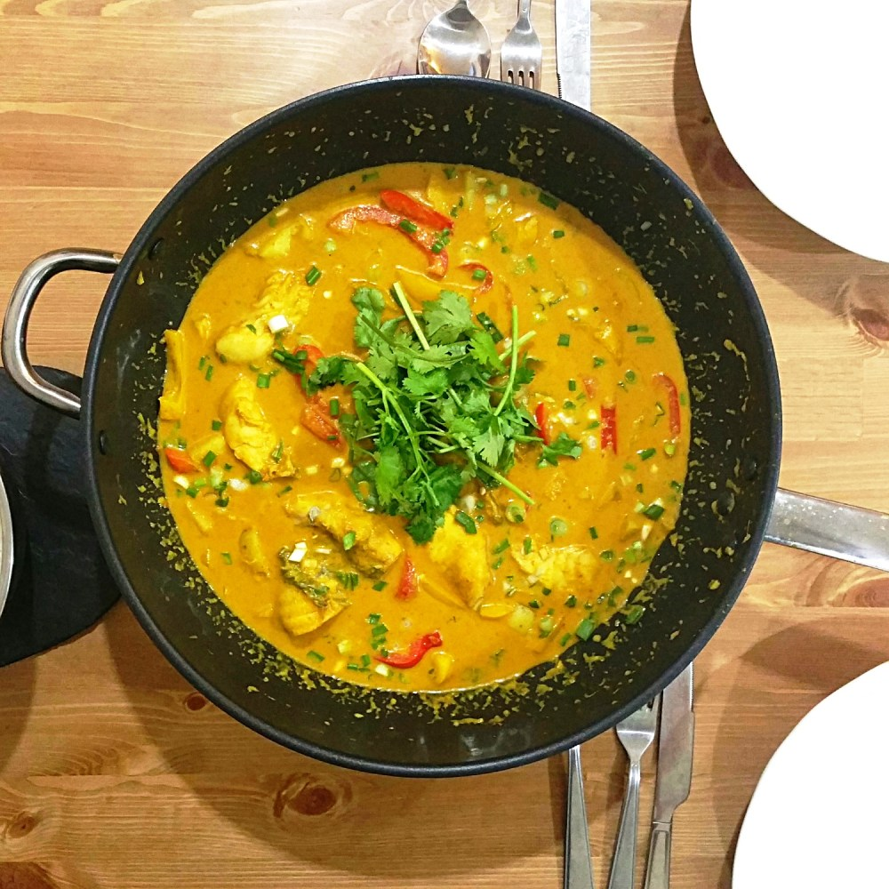 a big pot of Hoki poached in Thai yellow curry with potatoes and red bell pepper