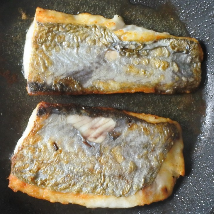 white fish frying in pan with oil