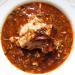 Chicken thigh atop Cajun stew with crispy skin garnish