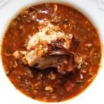 Chicken thigh atop Cajun stew with crispy skin garnish