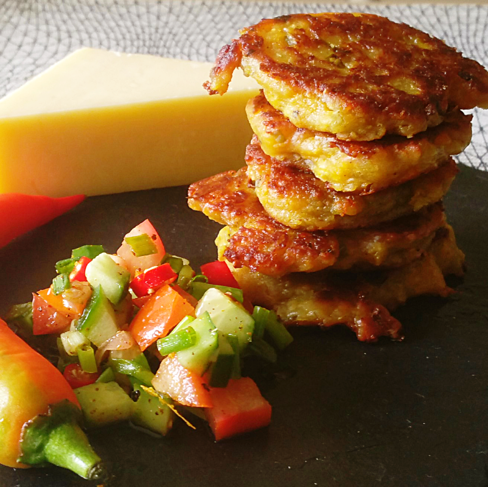 a stack of Indian cheese fritters next to a block of cheese and cucumber salsa