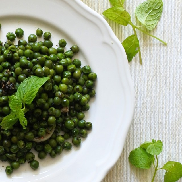 a plate of peas garnished with sprigs of fresh mint
