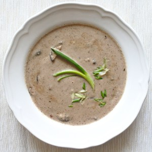 A bowl of pureed mushroom soup garnished with scallions