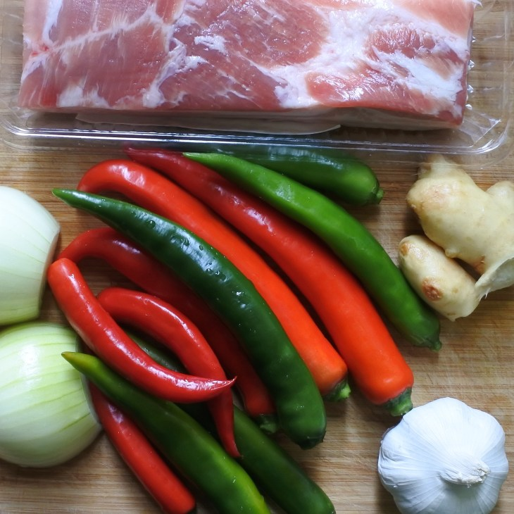 Pork belly, red and green chilis, garlic, onion and ginger on a wooden cutting board