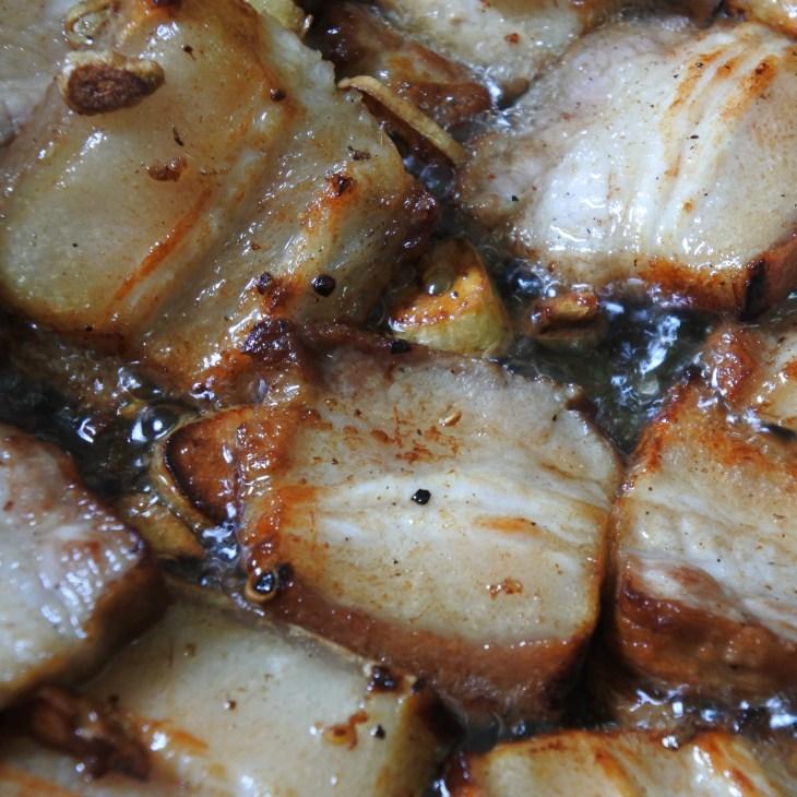 pork belly frying in a wok