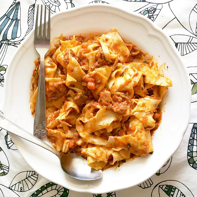 pork ragu tossed with homemade tagliatelle with fork and spoon