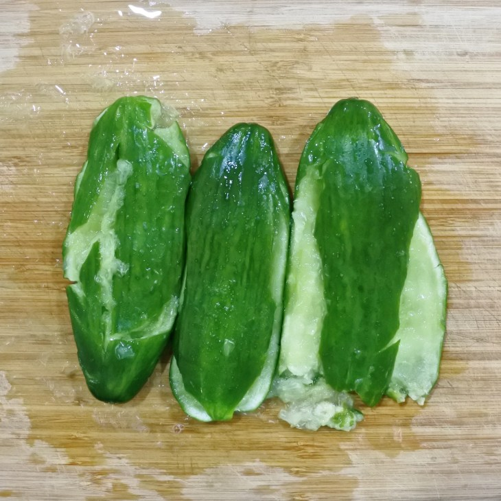 three smashed cucumbers on a cutting board