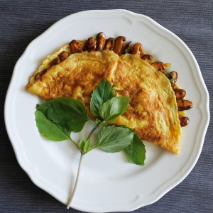 An omelette filled with mushrooms coated in a Thai chile sauce on a plate with a sprig of Thai Basil