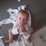 baby playing with unraveled toilet paper
