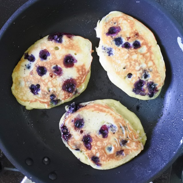 blueberry pancakes cooking in a pan