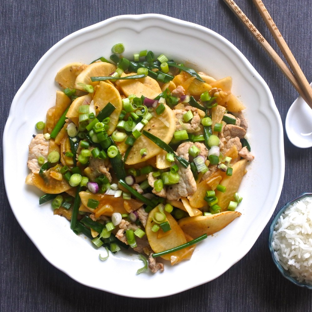 pork and pickled daikon stir fry garnished with chopped scallions and served with steamed rice