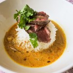 seared beef with fresh cilantro atop basmati rice in spicy soup