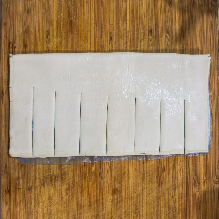 puff pastry folded in half with bottom half sliced