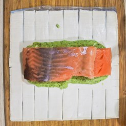 Basil mixture and salmon fillets on puff pastry