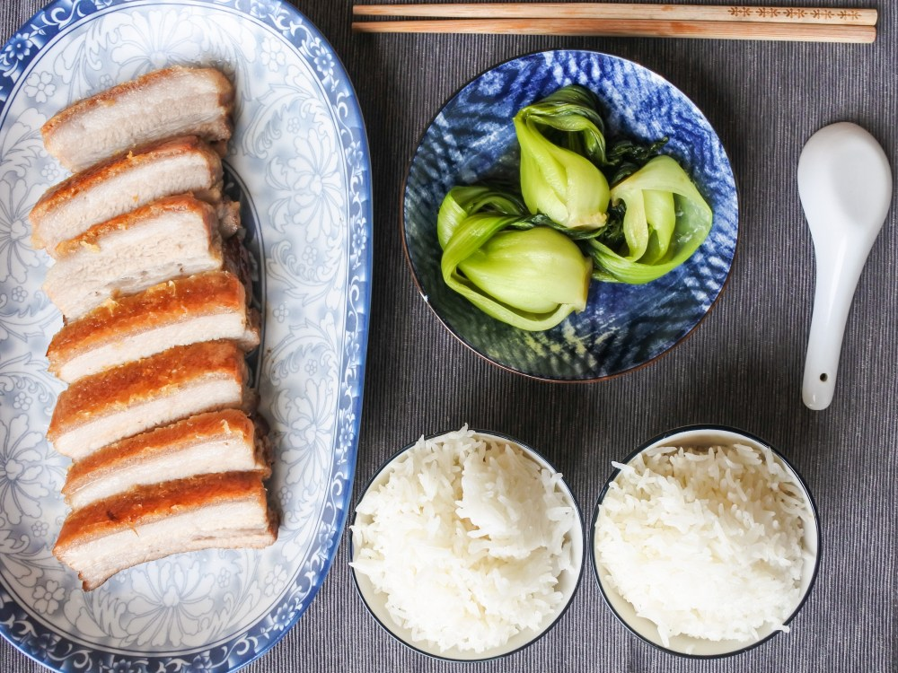 crispy pork belly served alongside steamed rice and bak choy