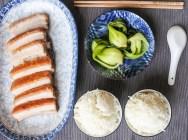 crispy pork belly served alongside steamed rice and bak choy