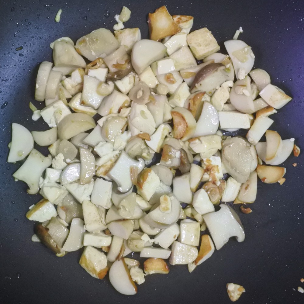 mushrooms and tofu frying in wok