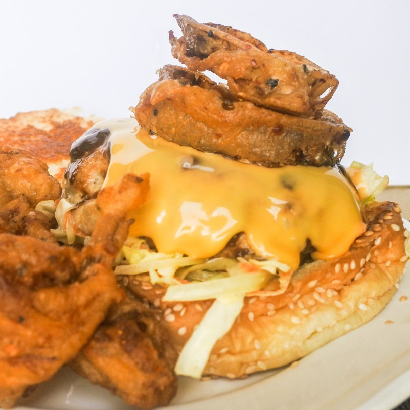 Armadillo Pork Burgers oozing cheese and topped with fried onion rings