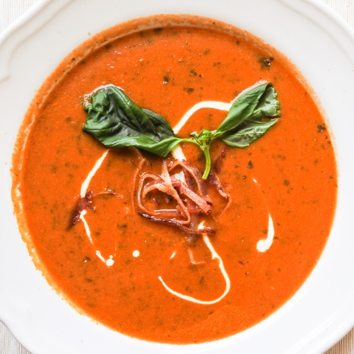 A bowl of tomato soup garnished with sliced bacon, basil leaves and a touch of cream