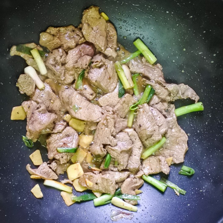 beef, ginger and scallions frying in wok