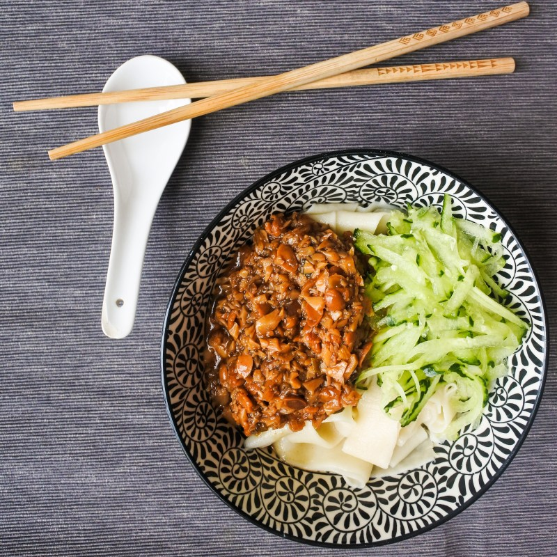 a bowl of Chinese noodles with grated cucumber and soy bean sauce with chopsticks and spoon