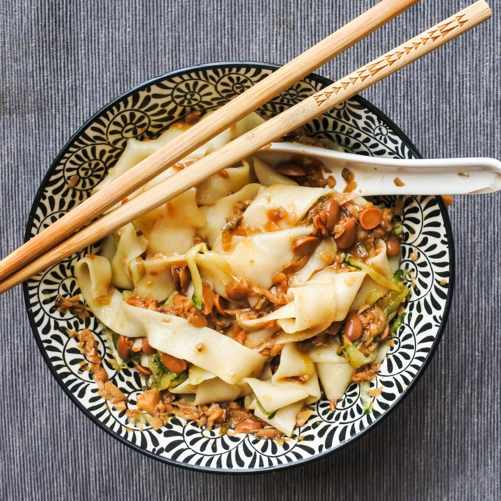 a bowl of Chinese noodles with grated cucumber and soy bean sauce tossed together