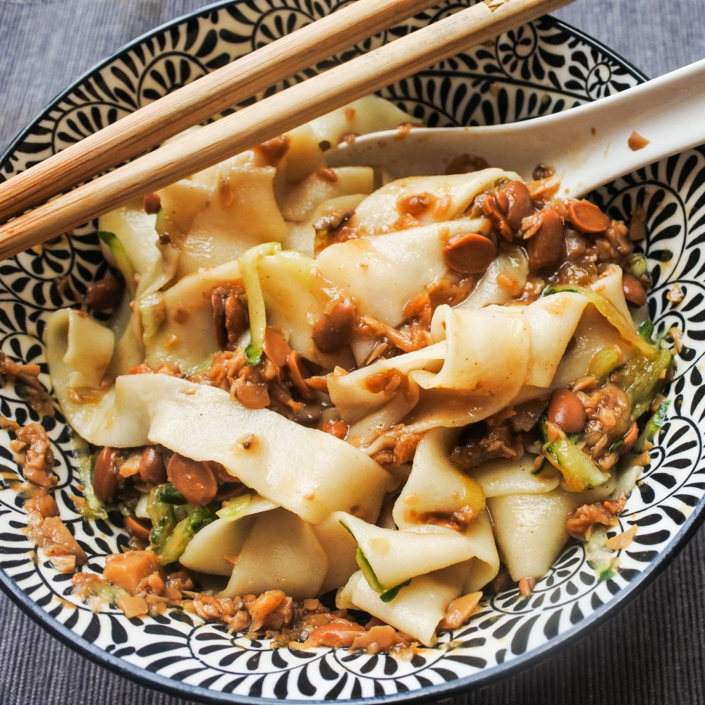 a bowl of Chinese noodles tossed together with grated cucumber and soy bean sauce
