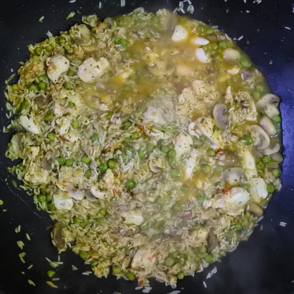 rice mixture simmering in chicken broth