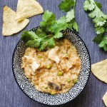 A bowl of arroz con pollo with tortilla chips