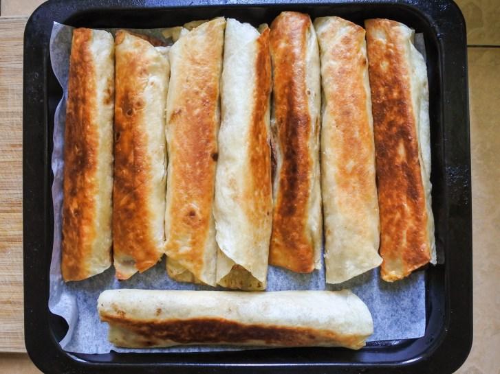 crispy burritos on an oven tray