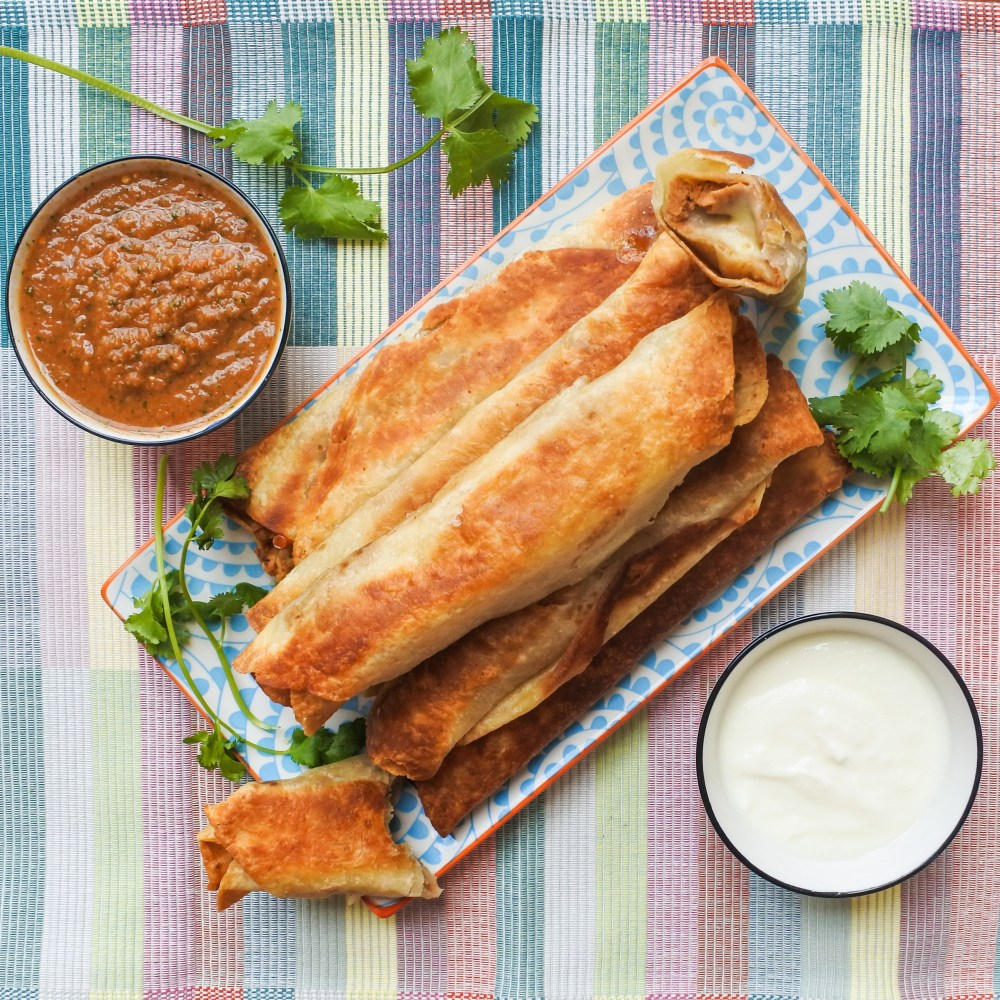 Crispy bean burritos on a plate with fresh salsa, cilantro and sour cream