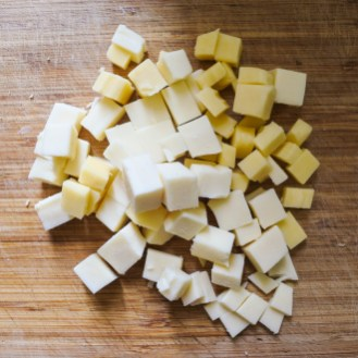 cheese cubes on a wooden cutting board