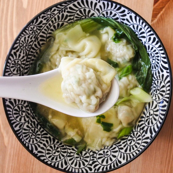 A bowl of wontons and bak choy in chicken broth