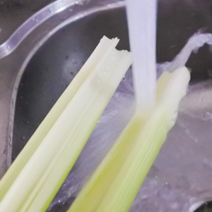 Leeks cut down the middle being washed under running water