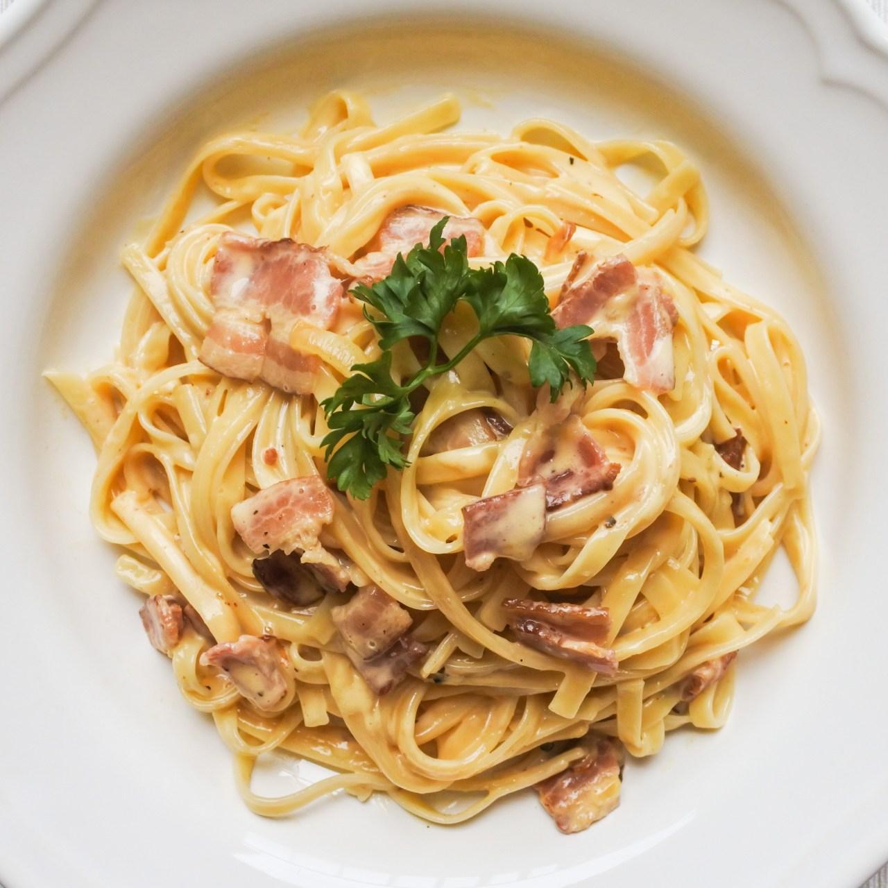 Pasta Carbonara garnished with a sprig of parsley