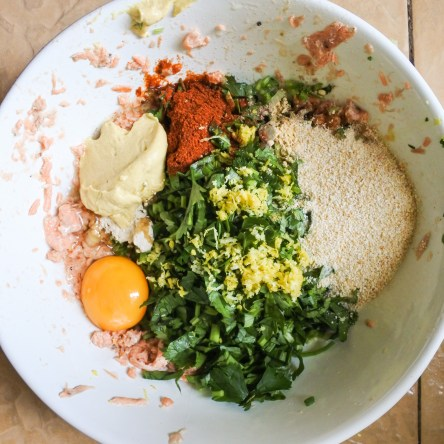 Combine salmon meat with chopped scallions, garlic powder, paprika, chopped celery leaves, breadcrumbs, egg, lemon zest, ginger powder, a pinch of nutmeg, Dijon, salt and a sprinkling of black pepper.