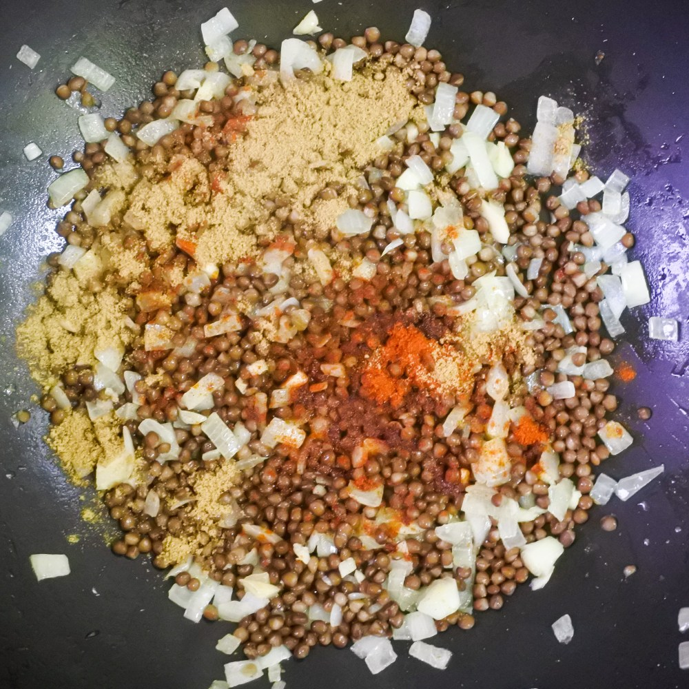 Lentil mixture frying in a pan with spice