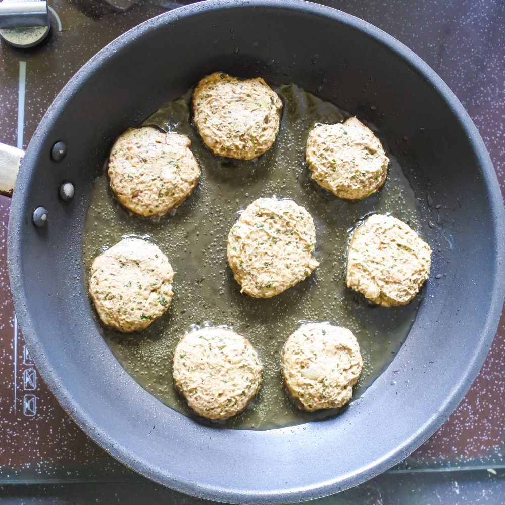 Raw lentil cakes frying in a pan