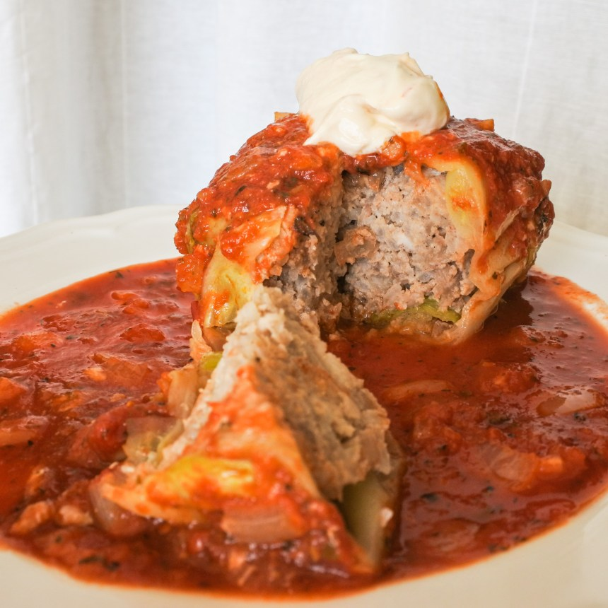 stuffed cabbage roll covered in tomato sauce and topped with sour cream