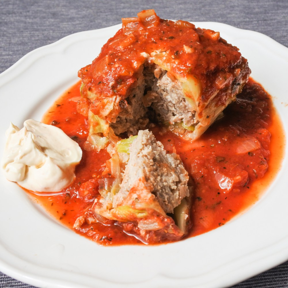 stuffed cabbage roll covered in tomato sauce with a side of sour cream
