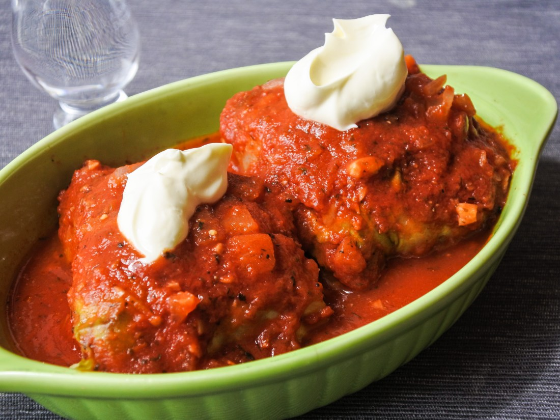stuffed cabbage rolls covered in tomato sauce and topped with sour cream