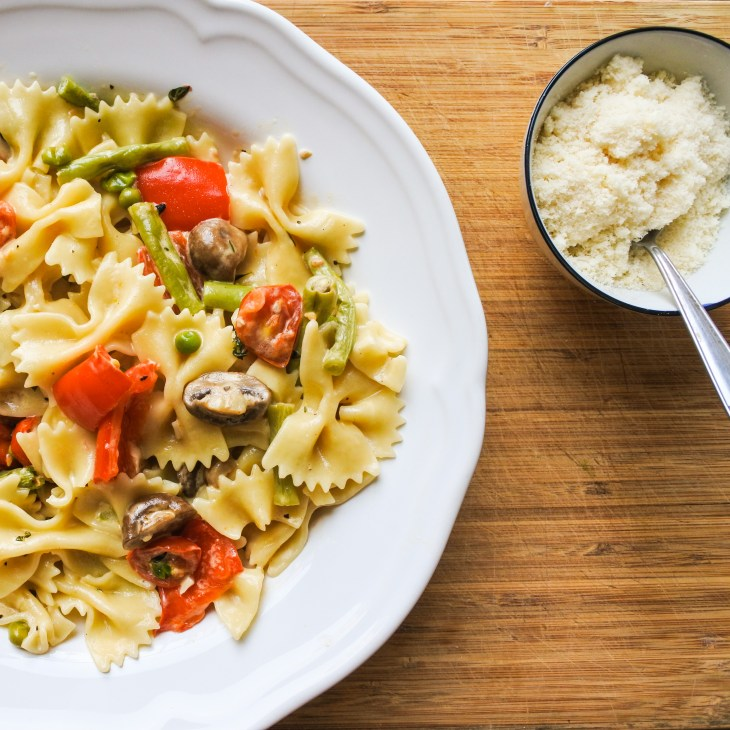 a plate of healthy pasta primavera served alongside grated Parmesan cheese