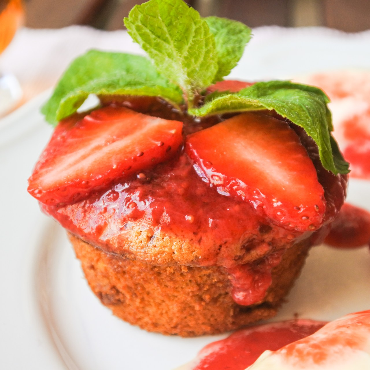 Dulce de leche cupcake topped with strawberry sauce, sliced strawberries and a sprig of mint