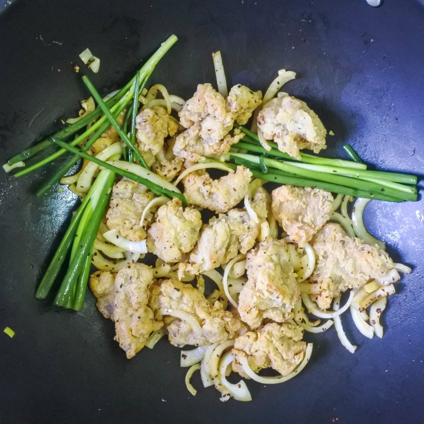 Sliced onions, scallions, and fried chicken together in a pan