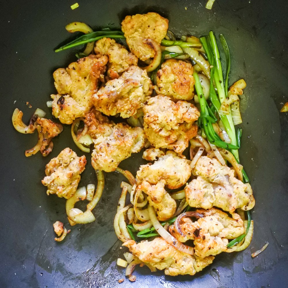 Fried chicken coated in chile oil and tossed with scallions and onions in a pan