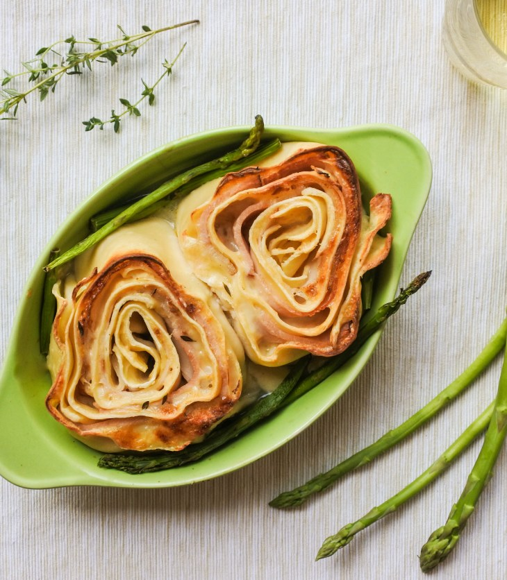 Rolled up pasta with ham and cheese served with asparagus in an oven dish alongside a sprig of thyme and glass of white wine