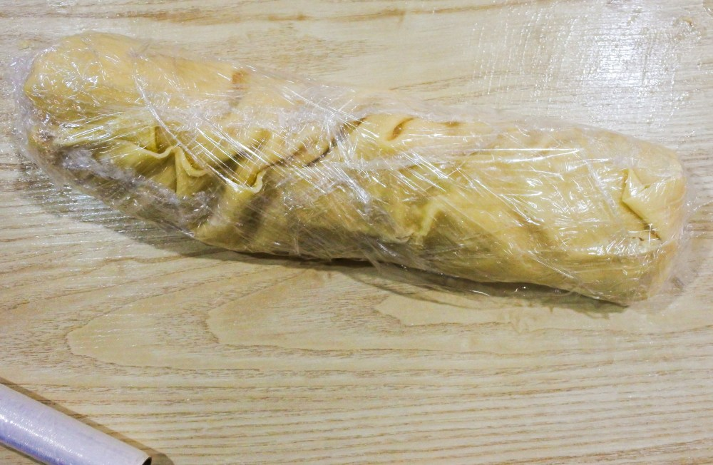 Rolled up pasta sheet wrapped in plastic