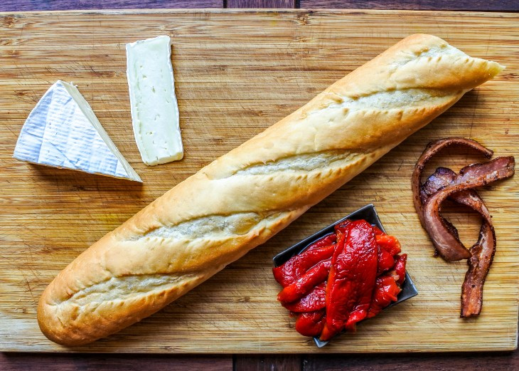 Brie cheese, baguette, roasted red bell pepper and strips of bacon on a wooden cutting board